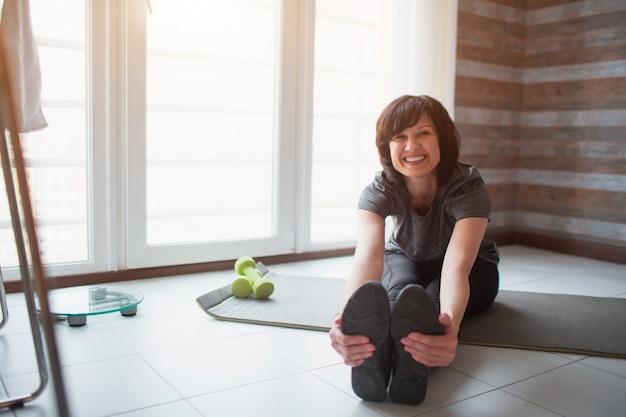 Adulto slim mulher tem treino em casa. pessoa madura positiva alegre que estica a parte superior do corpo para a frente em direção aos dedos dos pés e sorri. posando na câmera. tome cuidado com o corpo.