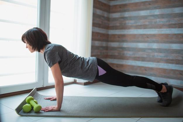 Adulto slim mulher tem treino em casa. vista lateral do forte modelo sênior bem construído fica na posição de prancha completa. alongamento para trás e corpo.