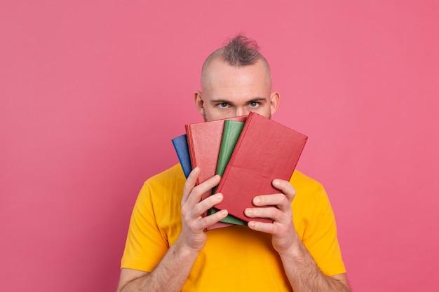 Adulto sorrindo com roupas casuais e barba abraçando os livros favoritos para si mesmo isolado na cor rosa