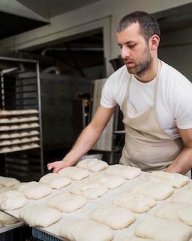 Adulto trabalhando em deliciosos pães frescos