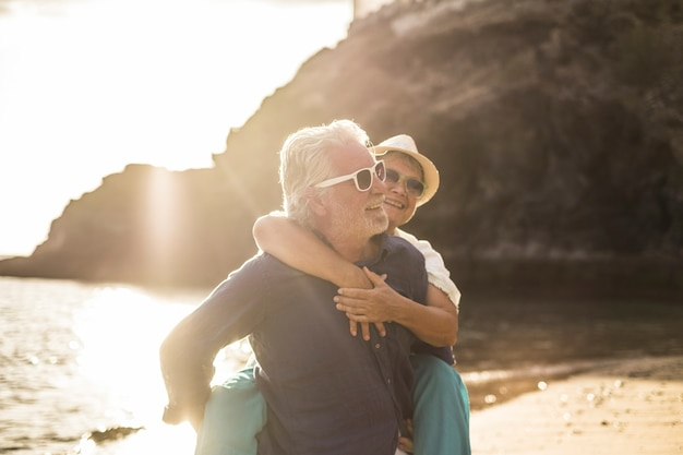 Adultos caucasianos casal apaixonado pelo homem carregando a mulher e ambos sorriem e riem muito