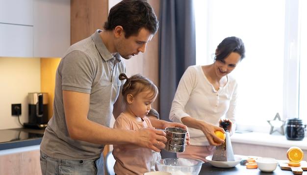 Adultos de tiro médio e criança na cozinha