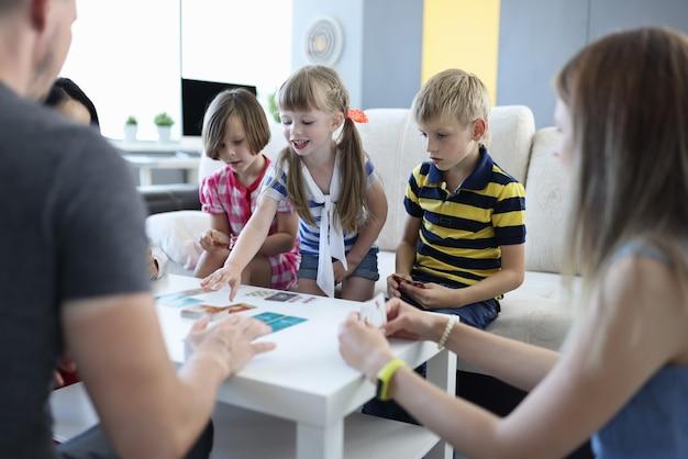 Adultos e crianças estão sentados ao redor da mesa em que se encontram as cartas de jogar. a garota pega uma carta com a mão.