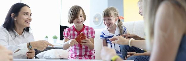 Adultos e crianças estão sentados ao redor da mesa segurando cartas de jogos e rindo alegremente