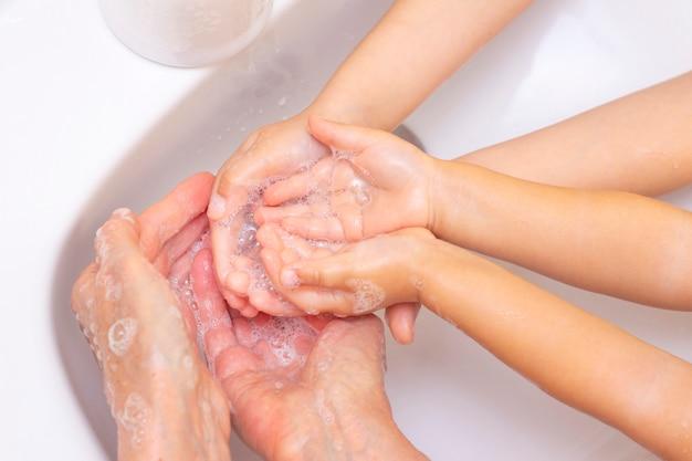 Adultos e crianças lavam as mãos. mãos em espuma de sabão antibacteriano. proteção contra bactérias, coronavírus. higiene das mãos. lavando as mãos com água. muitas mãos