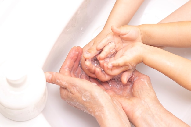Adultos e crianças lavam as mãos. mãos em espuma de sabão antibacteriano. proteção contra bactérias, coronavírus. higiene das mãos. lavando as mãos com água.