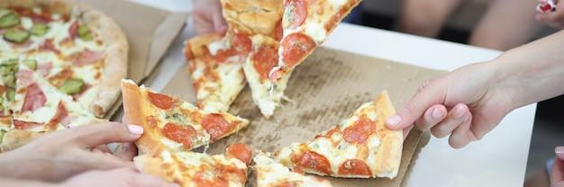 Adultos e crianças pegam fatia de pizza na caixa Foto Premium