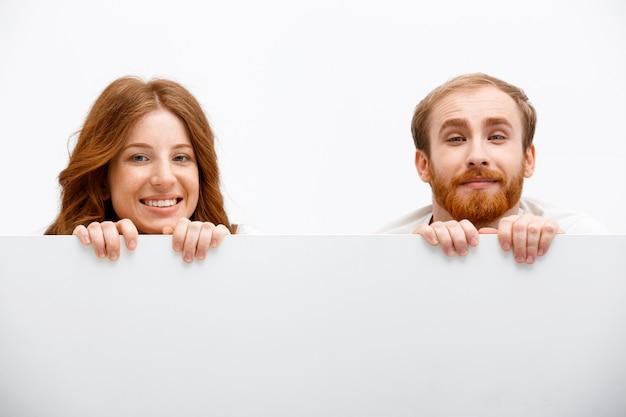 Adultos engraçados ruiva homem e mulher se escondendo atrás de mesa