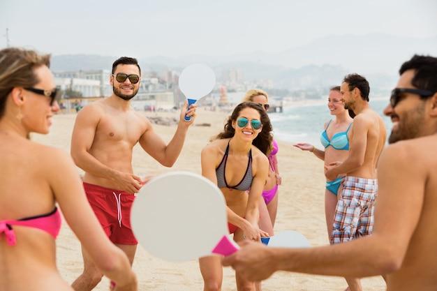 Adultos positivos com raquetes relaxantes na praia