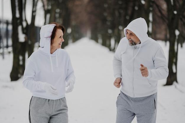 Adultos sorridentes de tiro médio correndo