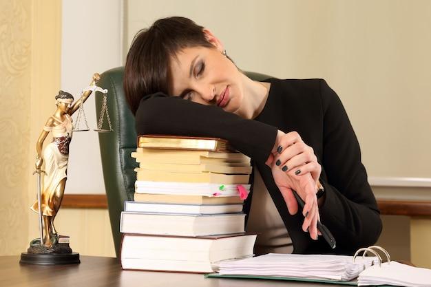Advogada cansada no escritório com livros e documentos