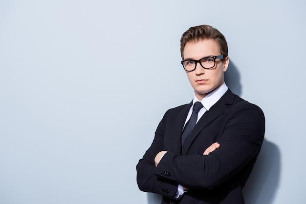 Advogado bem sucedido jovem bonito de terno e óculos no espaço puro com as mãos cruzadas. severo e áspero, rico e confiante, atraente e inteligente