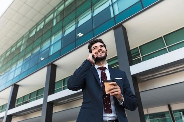 Advogado de baixo ângulo sorridente com telefone e café