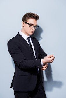 Advogado de jovem empresário bonito de terno está corrigindo as tintas de punho, ele fica no espaço de luz pura. tão maduro e viril, quente e confiante