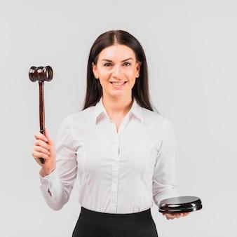 Advogado de mulher em pé com o martelo e sorrindo