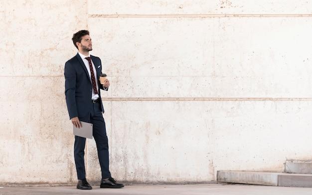 Advogado de vista lateral com tablet e café