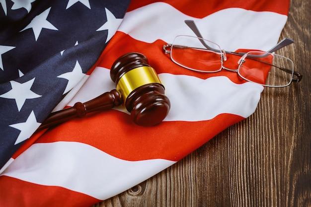 Advogado do escritório de justiça na mesa trabalhando martelo de juiz de madeira e óculos na bandeira americana