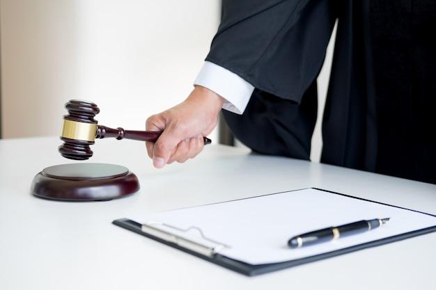 Advogado do juiz do sexo masculino em uma sala de audiência striking the gavel no bloco de som