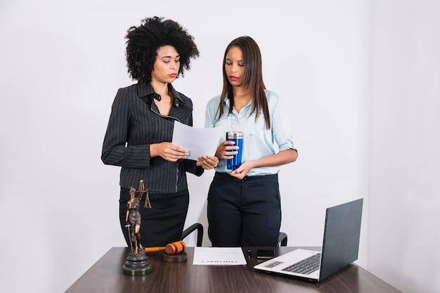 Advogado e assistente de pé à mesa com documentos
