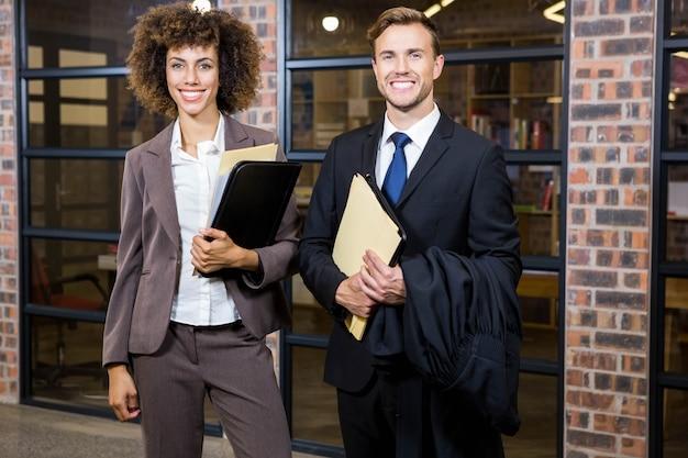 Advogado e empresária em pé perto da biblioteca com documentos no escritório