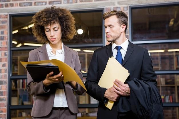 Advogado e empresária olhando documentos no escritório