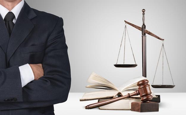 Advogado em pé com os braços cruzados, balança da justiça ao fundo