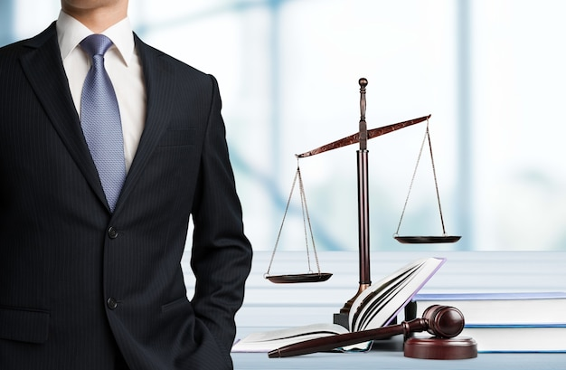 Advogado em pé perto da balança de justiça ao fundo