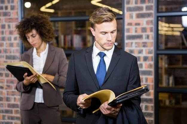 Advogado em pé perto de biblioteca e olhando documentos