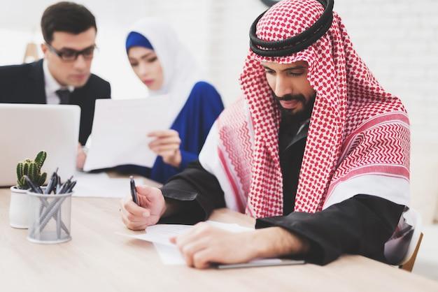 Advogado está falando com a mulher. árabe está escrevendo.