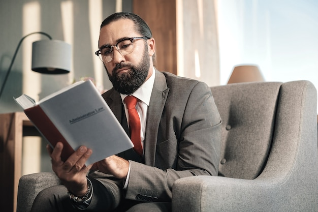 Advogado inteligente. advogado inteligente barbudo usando gravata vermelha e traje cinza lendo direito administrativo
