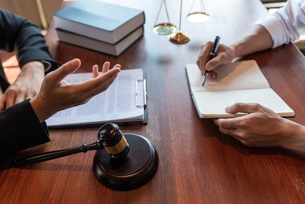 Advogado juiz, consultando papéis contratuais com um cliente no escritório