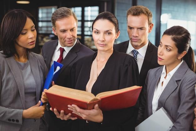 Advogado lendo um livro de direito e interagindo com pessoas de negócios