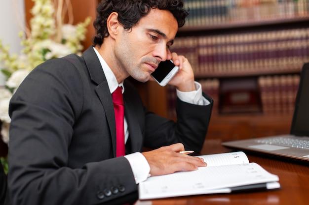 Advogado, lendo um livro e falando ao telefone