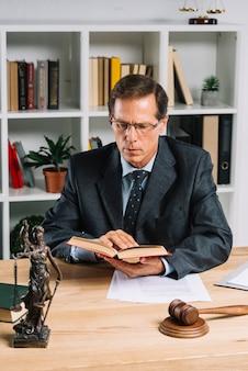Advogado macho maduro, leitura, livro, com, martelo, e, justiça, estátua, ligado, tabela madeira