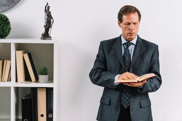 Advogado maduro lendo o livro de lei no escritório
