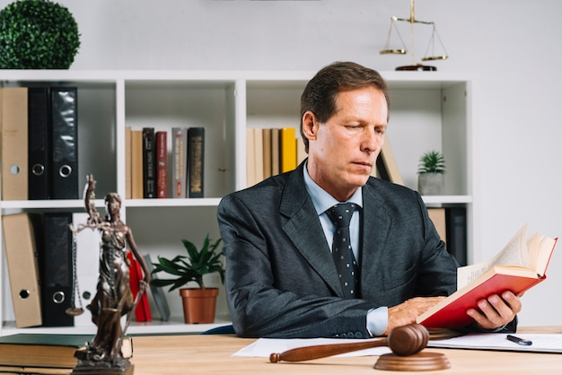 Advogado maduro lendo o livro de lei no tribunal