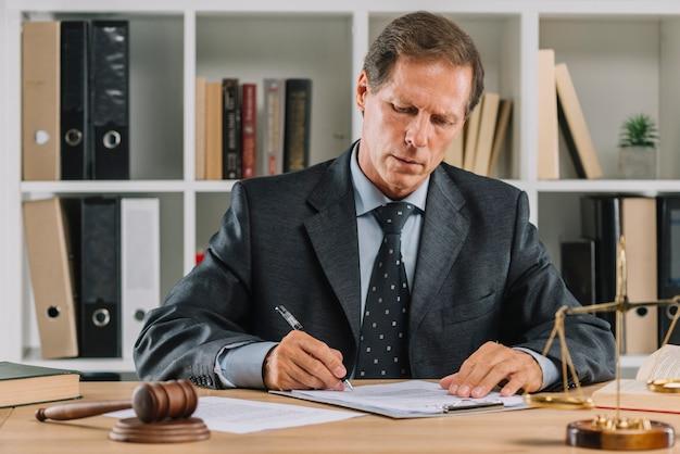 Advogado maduro sentado na sala de tribunal, assinando o contrato