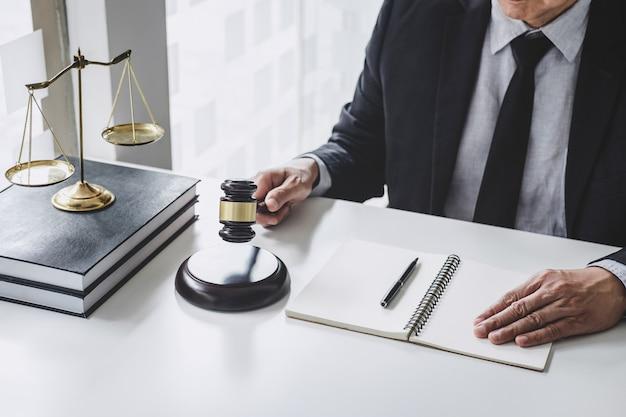 Advogado masculino com papéis, livros de direito, martelo de madeira e escala em uma tabela.