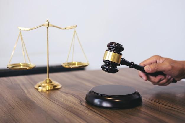 Advogado masculino ou juiz trabalhando com livros de direito, martelo, relatar o caso na tabela em moderno fora