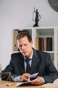Advogado masculino que inspeciona o contrato na sala do tribunal