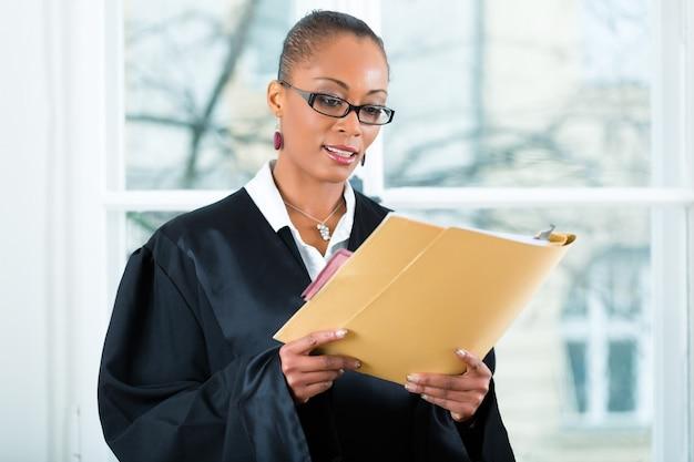 Advogado no escritório com dossiê em pé uma janela