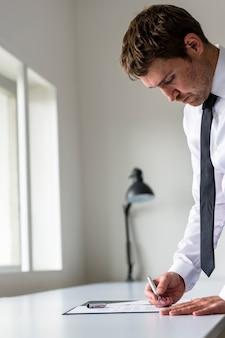 Advogado ou executivo assinando um contrato, colocado na mesa de escritório branca.