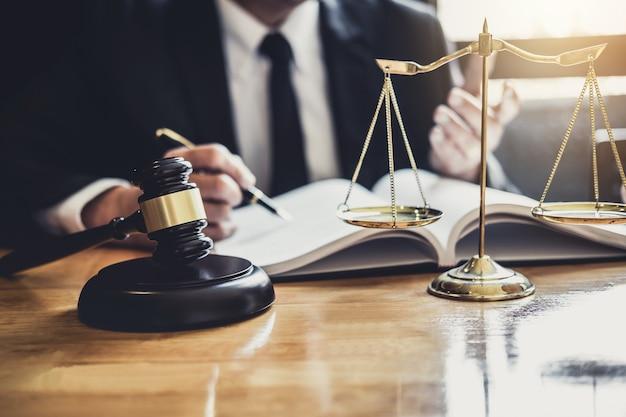 Advogado ou juiz trabalhando com documentos de contrato, livros de direito e martelo de madeira na mesa