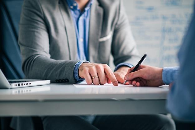 Advogado que mostra a um cliente onde assinar um documento legal, close-up.