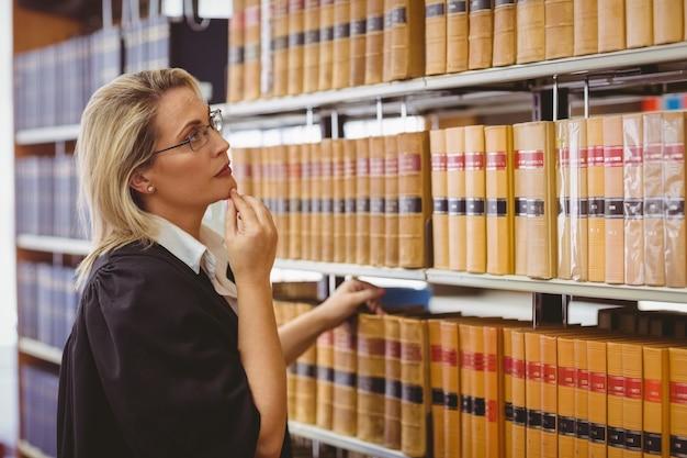 Advogado que usa óculos e procura um livro na prateleira