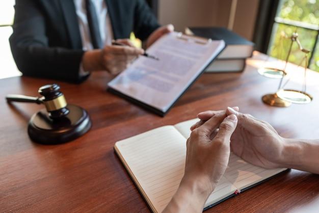 Advogado trabalhando com o cliente discutindo papéis do contrato com balança de latão