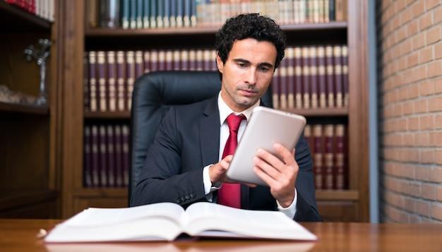 Advogado usando um tablet e lendo um livro em seu estúdio
