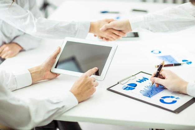 Advogados da empresa com documentos financeiros e tablet digital