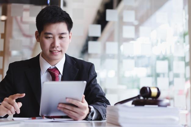 Advogados de negócios que usam o telefone celular para o cliente do contato com a escala de bronze na mesa de madeira no escritório. direito, serviços jurídicos, consultoria, consultoria, justiça.