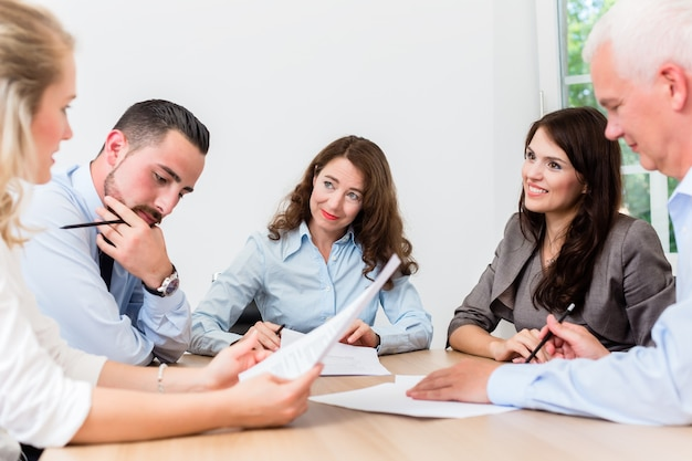 Advogados em reunião de equipe em escritório de advocacia, leitura de documentos e negociação de acordos